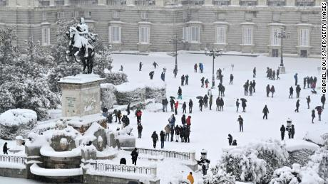 People enjoy the snow outside the Royal Palace in Madrid on January 9, 2021.