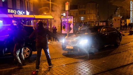 The official car escorting Belgium's King Philip turns around to dodge the demonstrators.