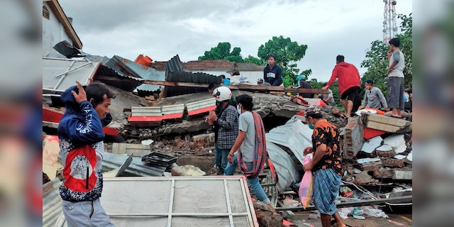 Residents inspect the ruins of a building destroyed by an earthquake in Mamuju, West Sulawesi, Indonesia, Saturday, January 16, 2021 (AP Photo / Yusuf Wahil)