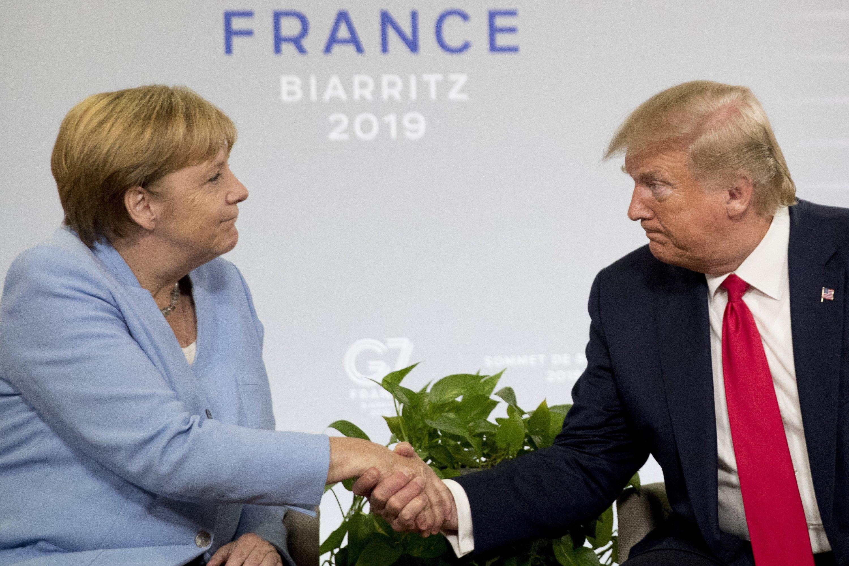 Президент США Дональд Трамп (R) та канцлер Німеччини Ангела Меркель потискують руку під час двосторонньої зустрічі на саміті