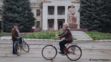 Жінка їде на велосипеді перед статуєю Леніна